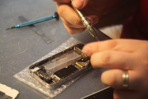 Figure 1: Cell phone repair technician takes apart an iPhone 4S in the shop's backroom. (Photo Credit: Joshua A. Bell)