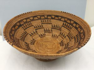 """Queen Isabella's Crown"". Petra Pico. Cat. No. E313084-0/ Acc. No. 064687. Smithsonian National Museum of Natural History.  Diam.10.5"" x 5"" h. Coiled weave, 3-rod juncus reed foundation. This basket was woven by Chumash weaver Petra Pico, (1834-1902) in Ventura County, CA., the last basket she wove before losing her eyesight. According to collection history notes Petra named this basket and imagery, ""Queen Isabella's Crown"", clearly indicating Spanish influence, as well as the pedestal which became present in Chumash basketry during the California Mission period.  Accessioned on 24/02/1920 by Miss Ella. F. Hubby."